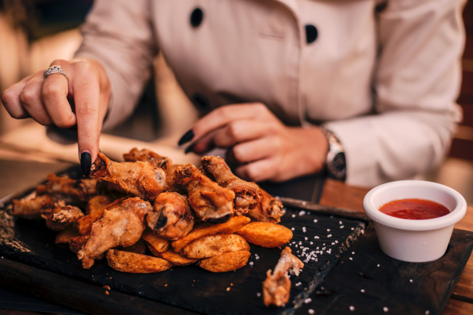 Close-up of girl's hands eating chicken wings