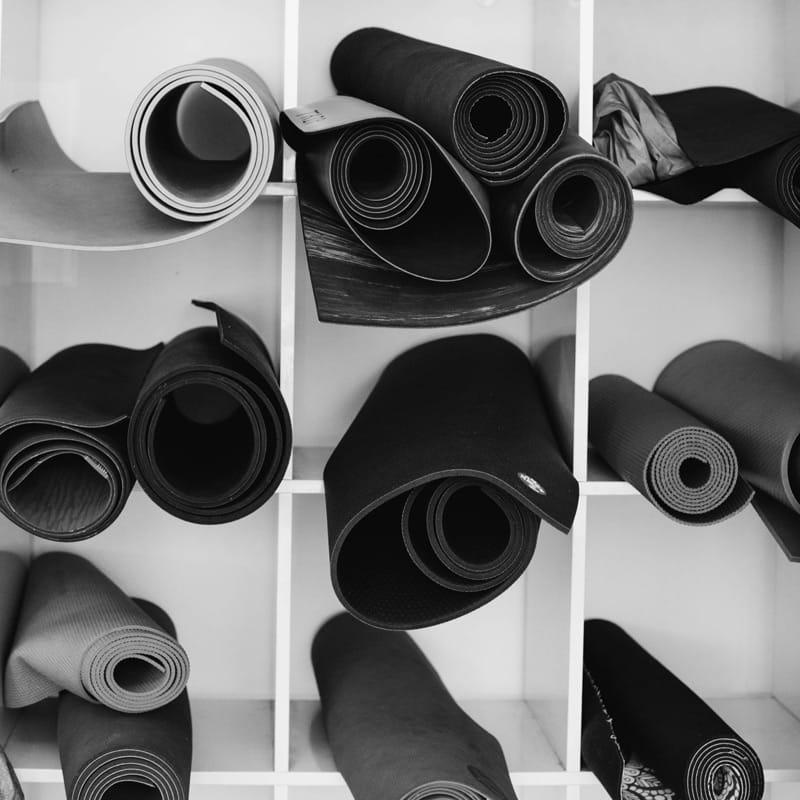 Verschillende soorten yoga matjes in een kast
