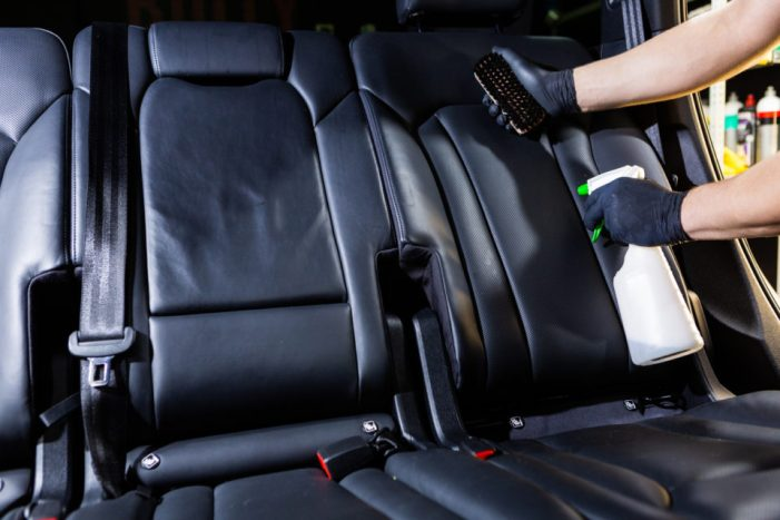 Worker spraying cleaning solution on car upholstery.