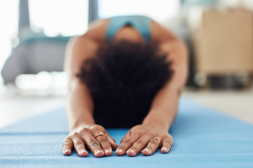 Shot of a woman doing yoga at home