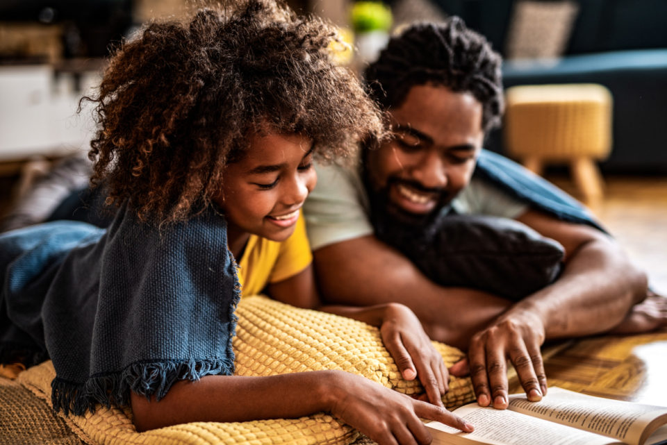 Father and daughter reading a book together.