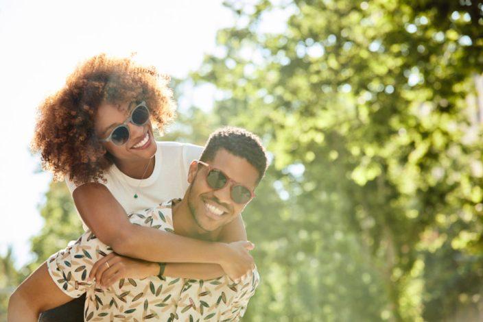 Young couple enjoying piggyback ride on sunny day.