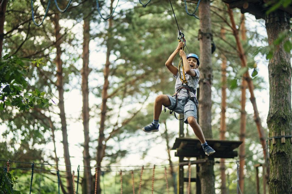 Boy hanging on zipline course