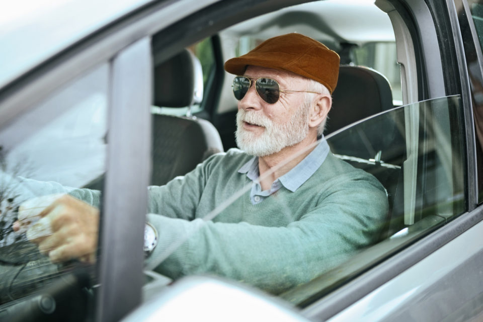 Senior man with sunglasses sitting in car driving windows down
