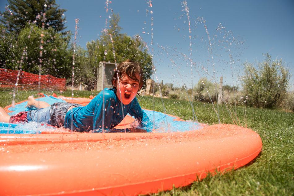 Young child sliding down backyard slip 'n slide