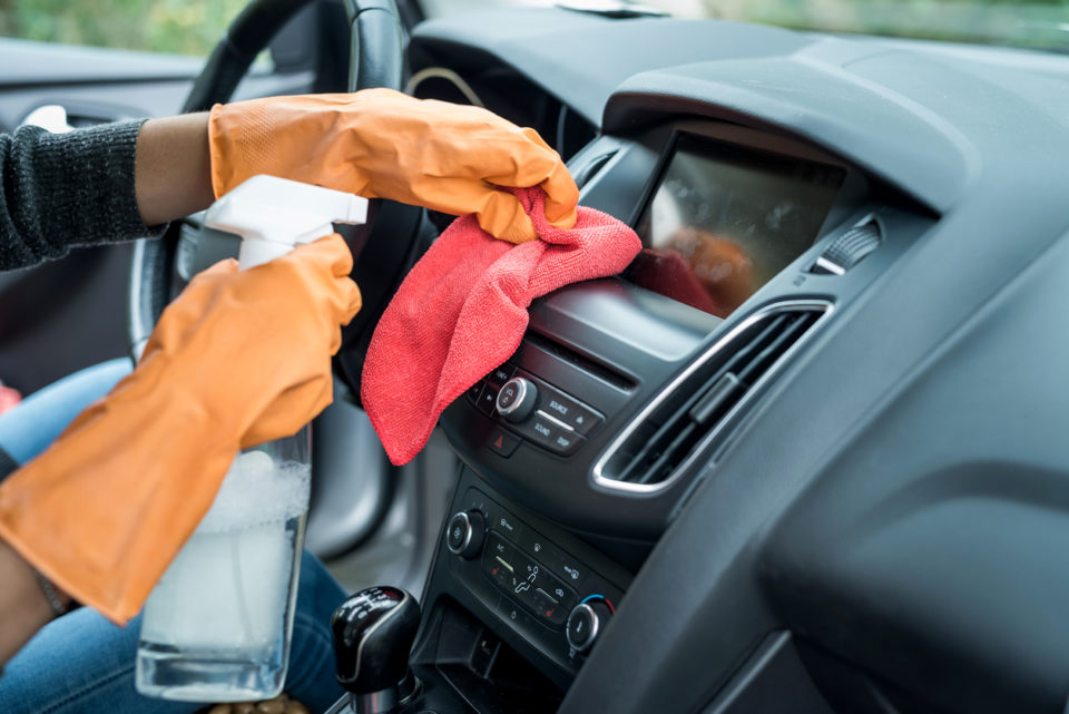 person with gloves on cleaning their car