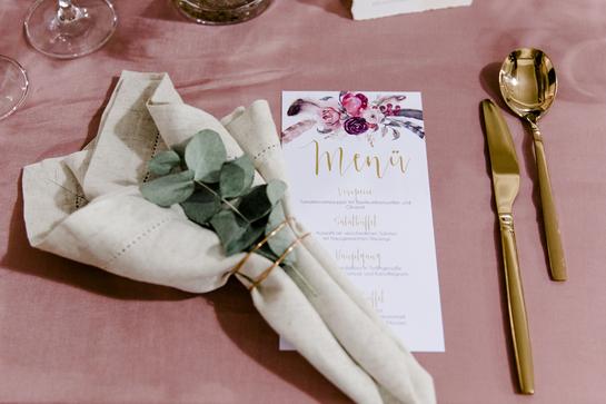 Menükarte auf rosa Tisch mit Besteck in gold