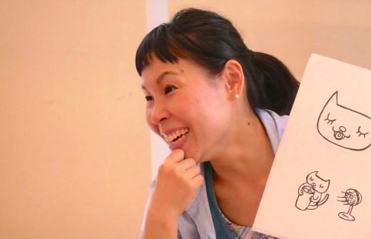 片岡まり子先生が絵本を持って笑っている