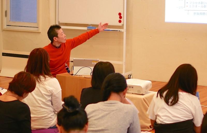 壁に写るスライドを指差して説明をしている高尾先生