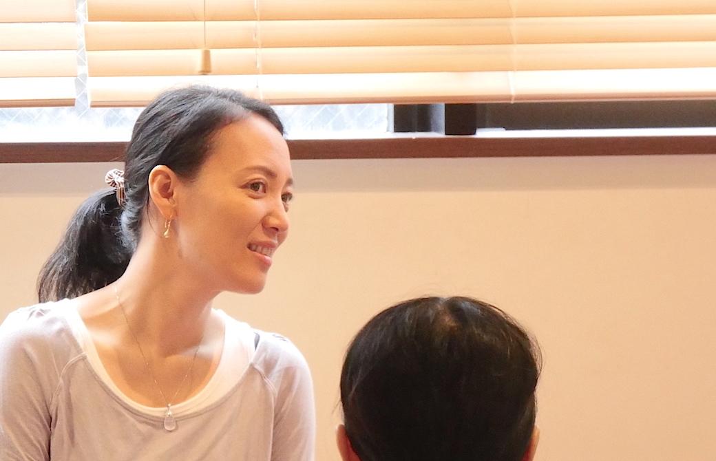 真理先生が笑顔で生徒さんの話を聞いている横顔