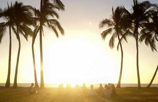 ハワイの朝日の下でヨガをしている様子