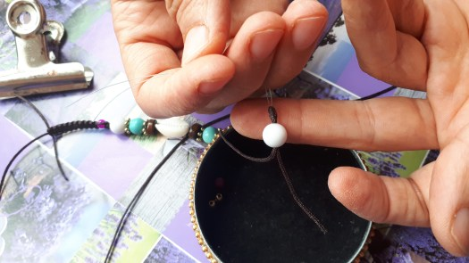 Step 6 to put a bead in the thread of a macrame bracelet by ShopCanarias.es