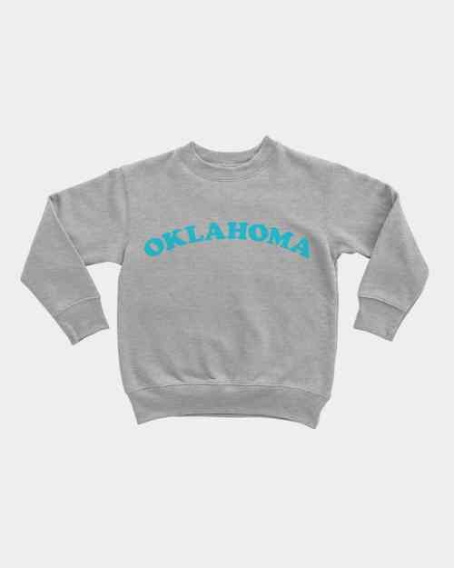 A grey kids pullover with Oklahoma written across the front in blue