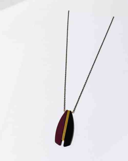 A gold chain necklace with maroon feather pieces on the end