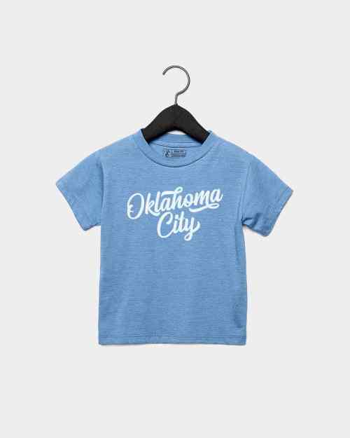 A mockup of a blue kids fit shirt with Oklahoma City printed in white ink