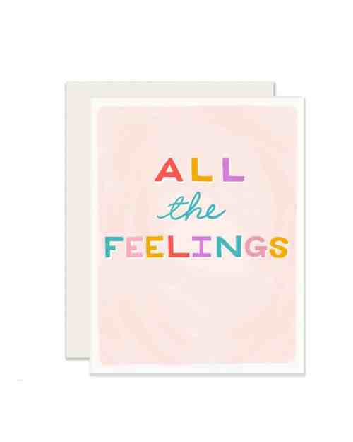 A pink card with All the Feelings written on the front in rainbow colors
