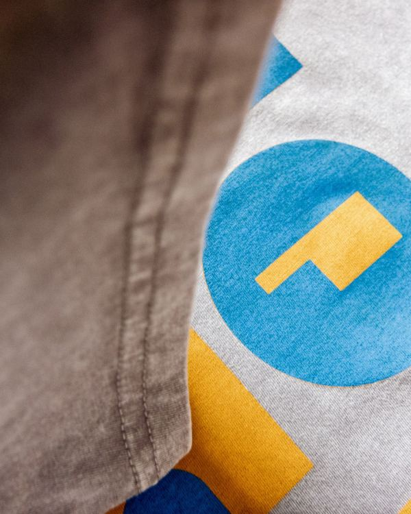 A photo of a grey tee shirt that says Oklahoma in yellow and blue ink. The letters are made out of geometric shapes.
