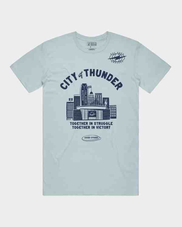 light blue tee shirt with illustration of the Oklahoma City skyline including the Devon Tower, Leadership Square & Chesapeake Energy Arena, home of the Oklahoma City Thunder. Shirts reads City of Thunder; together in struggle, together in victory