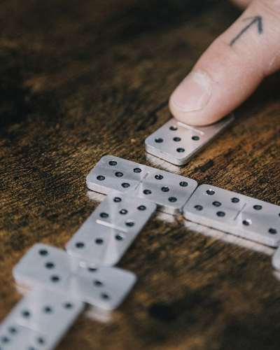 A hand configuring a set of metal dominos to play