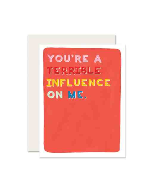 A white and red paper card that says 'You're a terribel influence on me.'