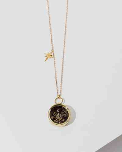 A brass chain necklace with a black compass on the end