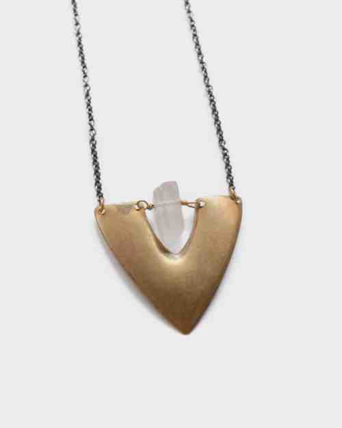 A photo of a Crystal Shield Necklace with a brass plate and center stone