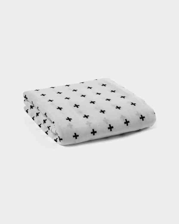 A mockup of a white swaddle with swiss crosses printed on it