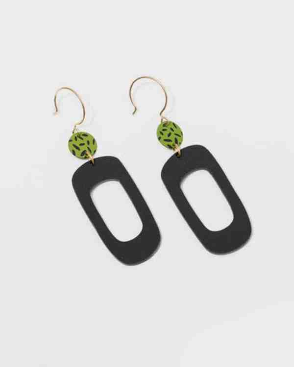 Brass earrings with green stones and black pendants hanging from them