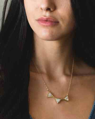brass necklace with white stone triangles hanging from it
