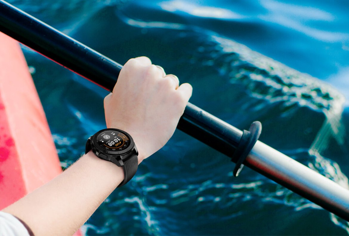 Right arm of a woman in a red kayak wearing a 42mm Midnight Black Galaxy Watch on her wrist.