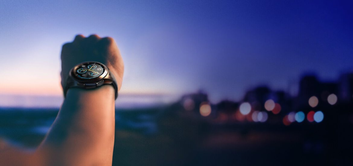 A 42 mm Midnight Black Galaxy Watch on an unknown person's wrist with a blurred sunset and city view in the background.