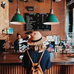 Girl in a brown hat wearing a brown backpack facing a counter in a cafe