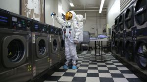 A traveler using a laundromat. Photo via Factinate.com.