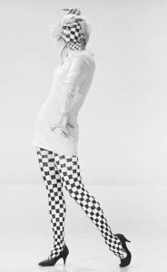 1967. An iconic look. Dancer Kathy Gale wears a mini skirt dress with checkerboard tights and some mod cosmetics work. Photo via nydailynews.com.