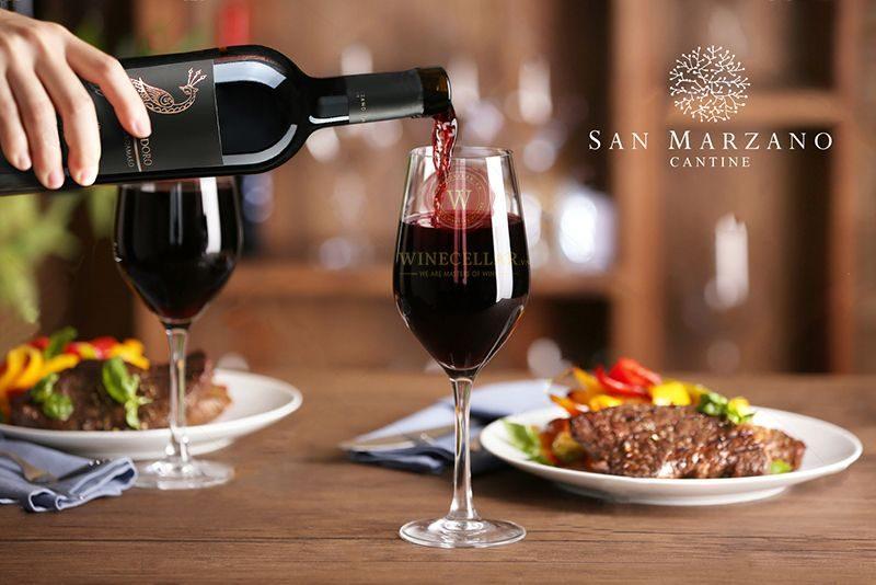 Rót ly rượu vang con công Vindoro Negroamaro Salento trên bàn tiệc