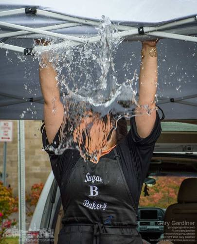 Sugar B Bakery's Angela empties water from the folds of her shelter after a rain squall dumped heavy rain on the Uptown Westerville Farmers Market.