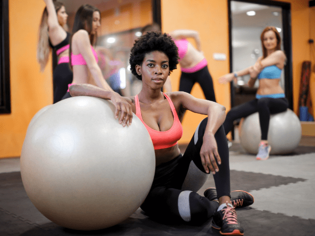 A black woman at a gym next to a fitness ball