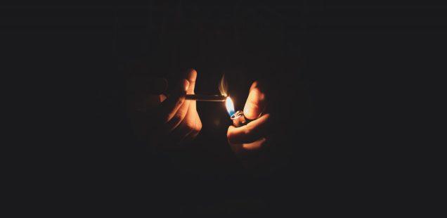 a person lights a cigarette in the dark