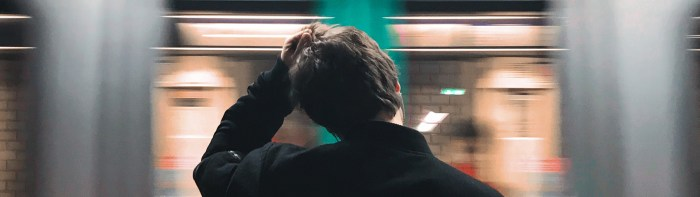 Image of man scratching head while subway train whizzes by