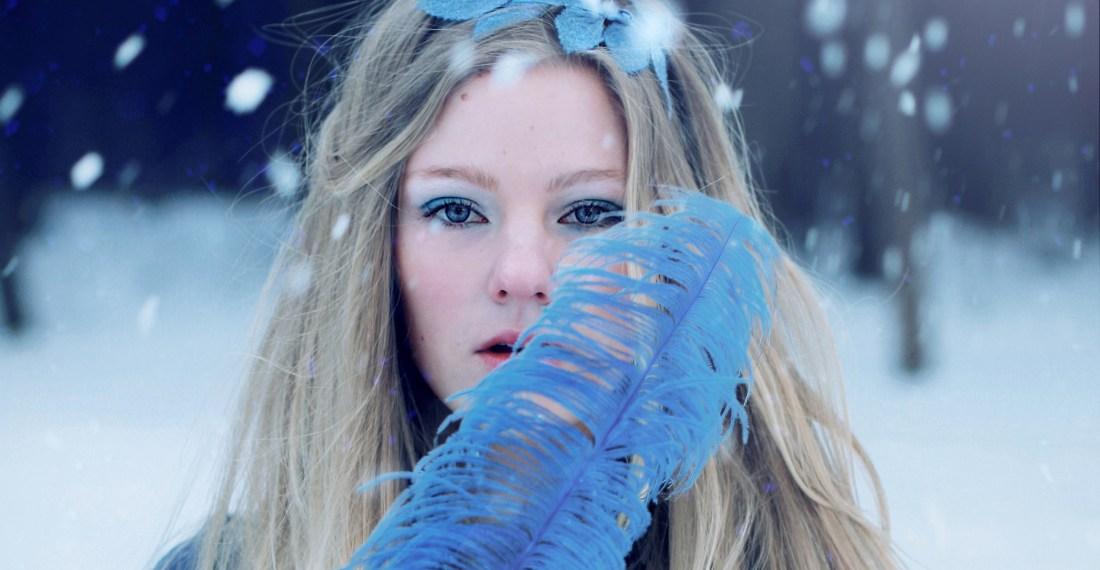 winter portrait of a blond girl with blue make up throwing snow