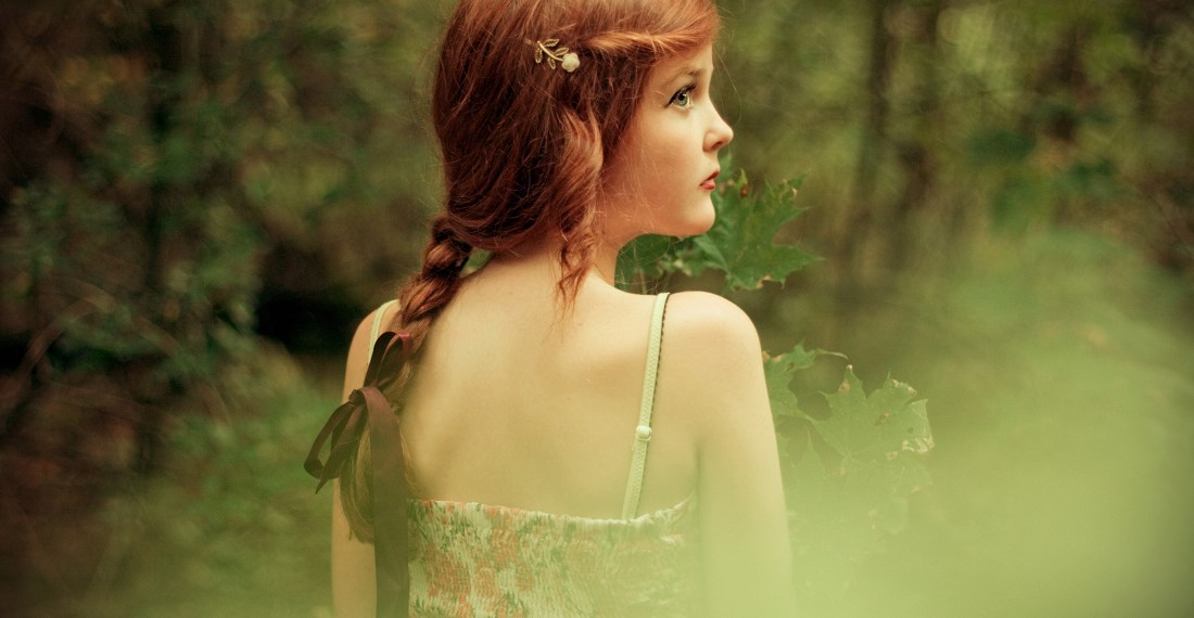 girl with red hair in a forest