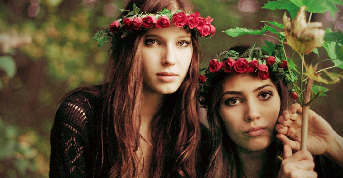 two dark haired girls in a forest with red flower crowns