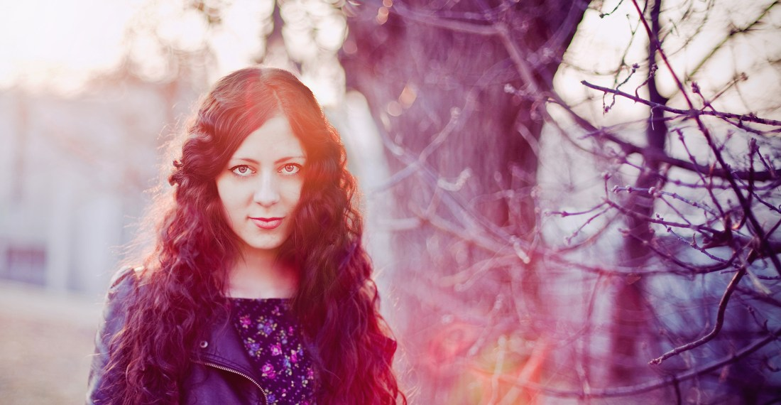 photographer Aiste Tiriute, girl with dark curly hair and a leather jacket with sunset and trees in the background
