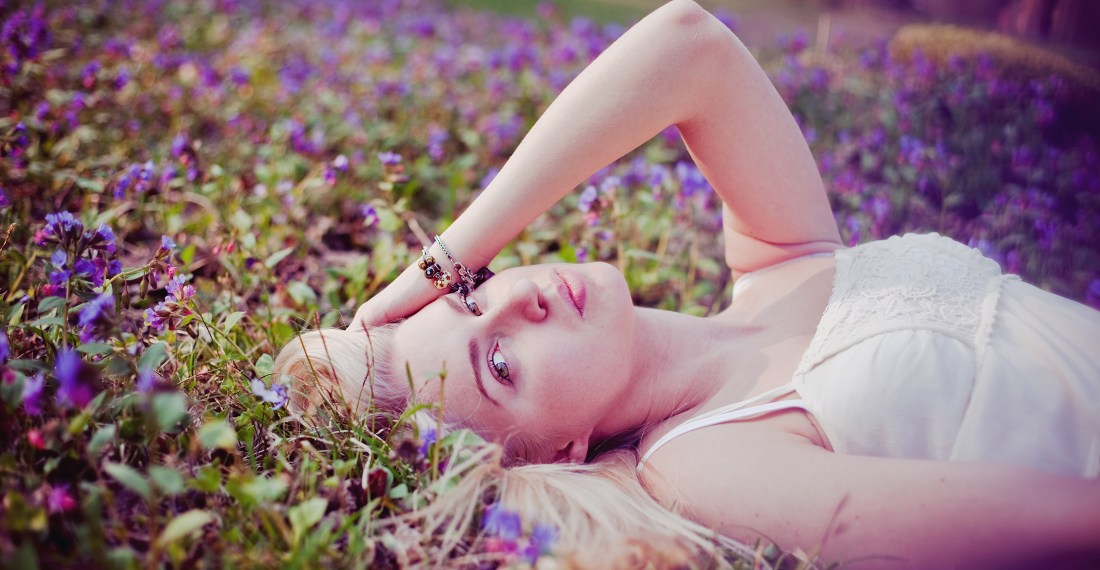 portrait of a blond girl lying in pink flowers