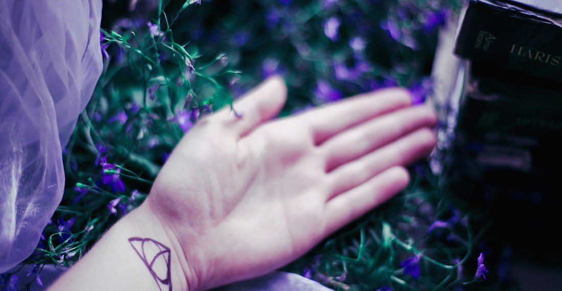 dreamy close up of a hand with the deathly hallows symbol