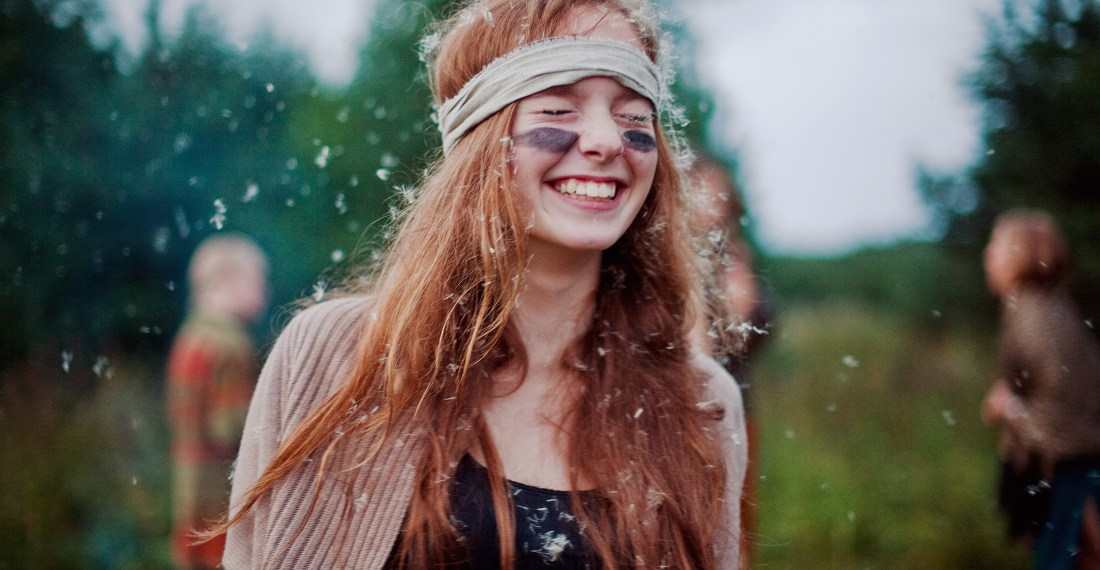 girl with camouflage make up and headband laughing