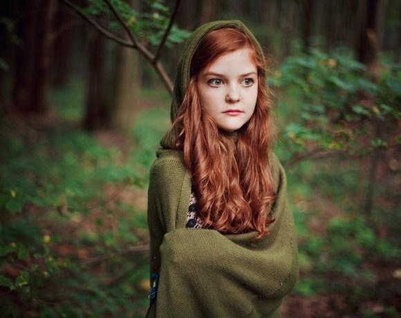 redhead cute girl in a green elvish cape in a forest