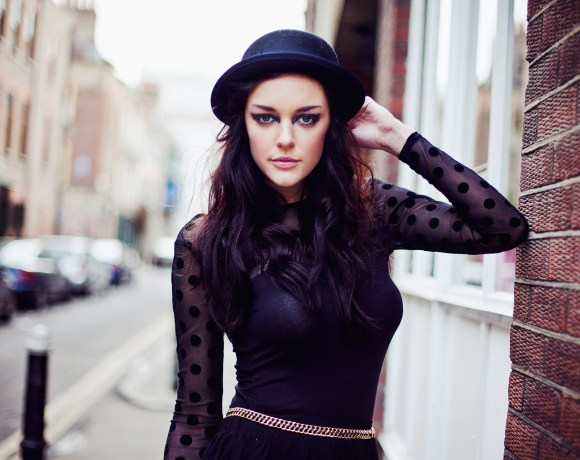 dark haired girl in mesh dot black top and hat