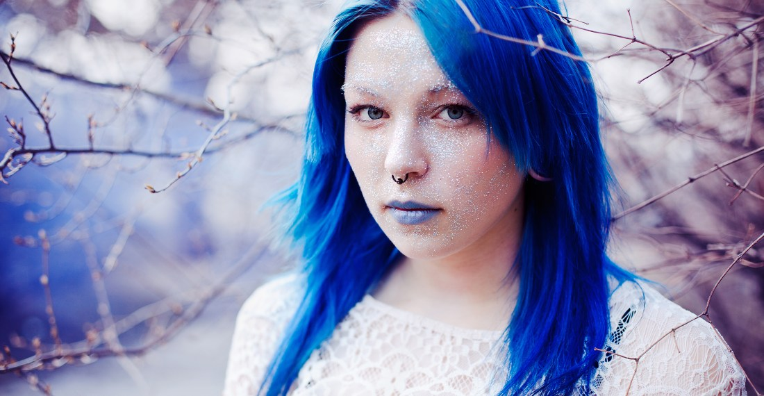 girl with bright blue hair and lips with glitter on her face in winter background with blue smoke