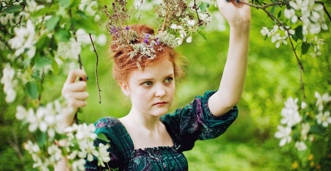 girl with red hair in the forest with blooming trees